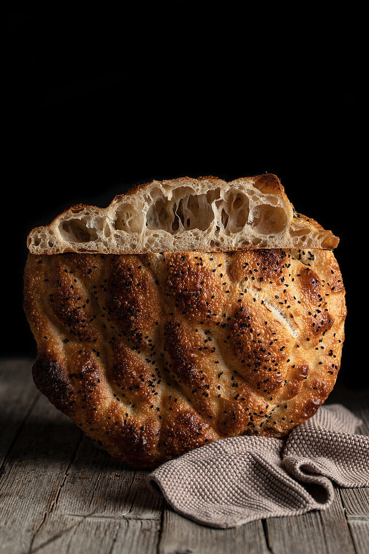 Fresh appetizing braided round bread with seeds placed on wooden table with napkin on black background