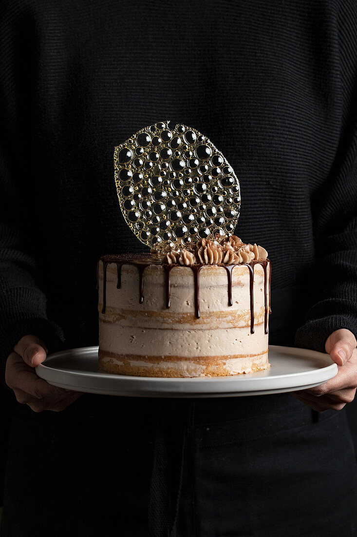 Unrecognizable person holding a festive cake with chocolate filling and frosting and silver isomalt decoration