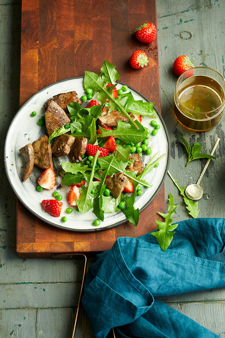 Fried venison liver on a dandelion salad with strawberries