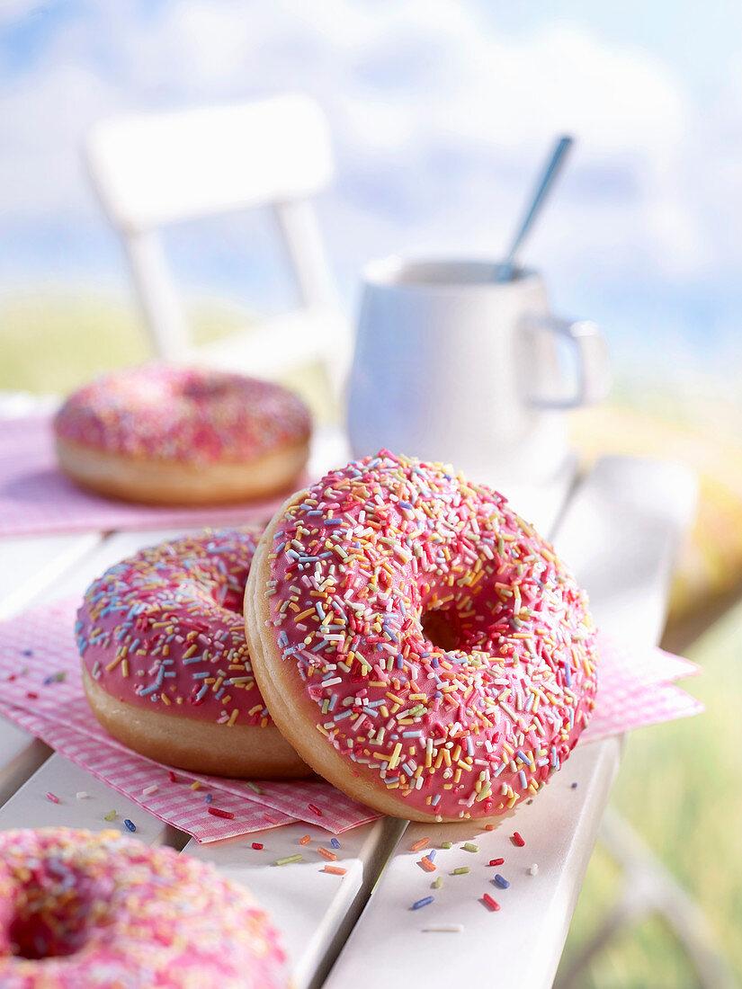 Donuts mit rosa Zuckerglasur und bunten Streuseln auf Gartentisch