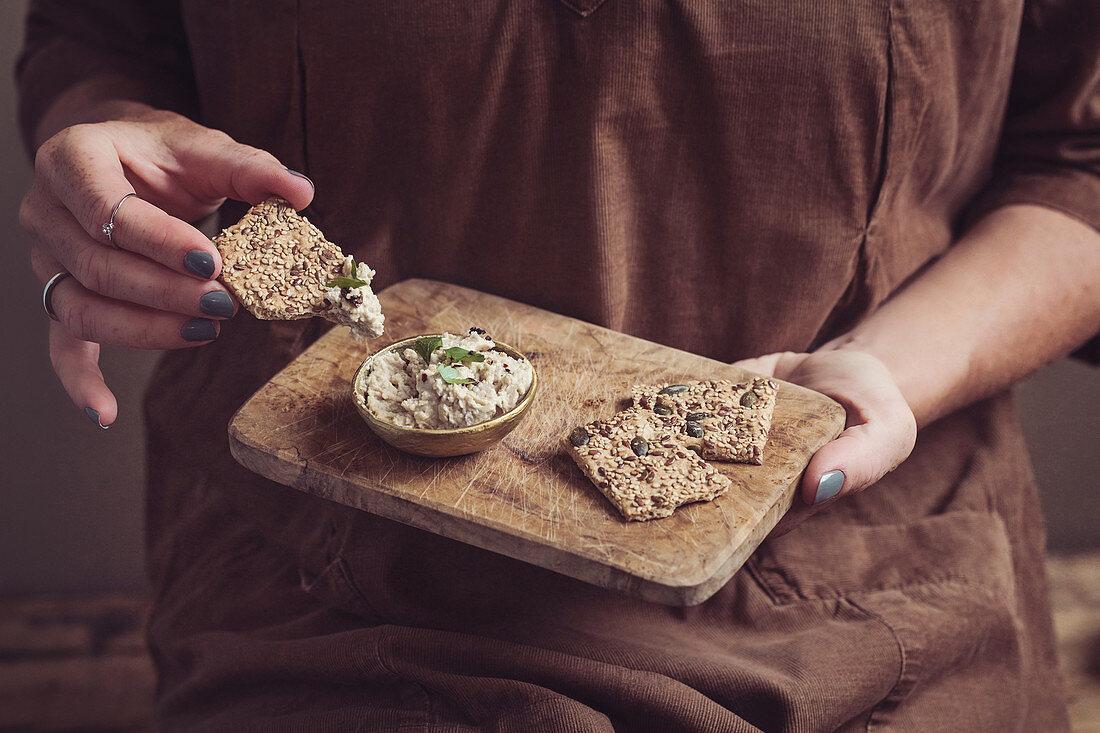 A woman eating baba ganoush (eggplant dip)