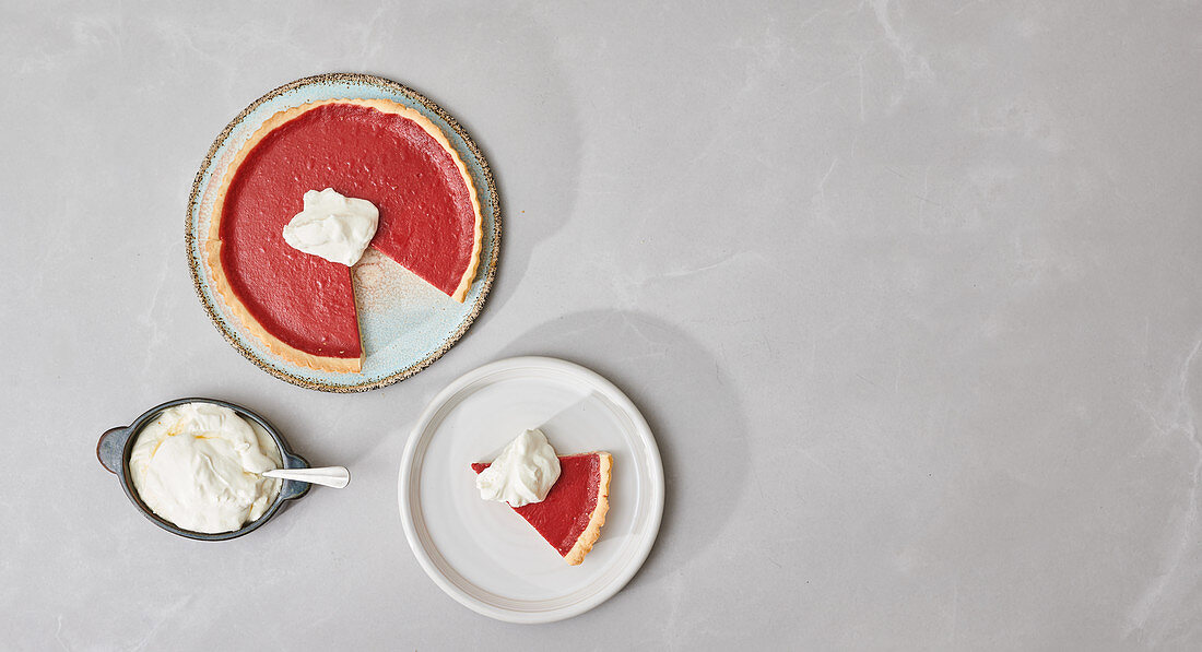 Cranberry pie, cut and served with cream