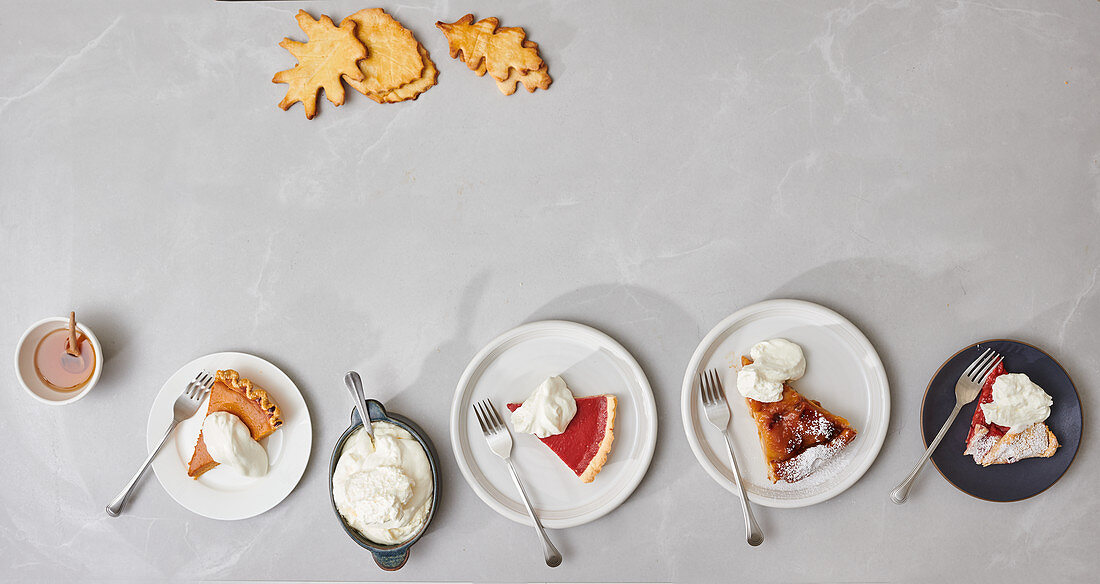 Slices of pumpkin pie, cranberry pie, tarte tatin and rhubarb galette on plates