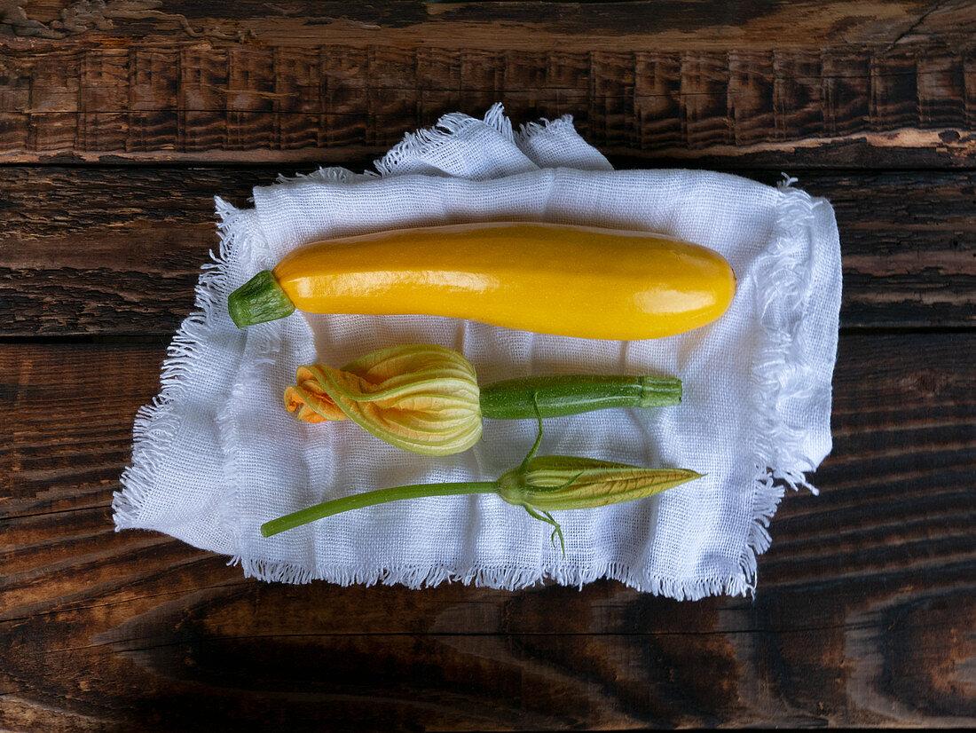 Fresh yellow zucchini and zucchini flowers on a linen cloth