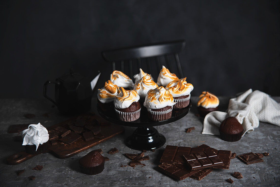 Chocolate muffins with Italian merinue on grey table