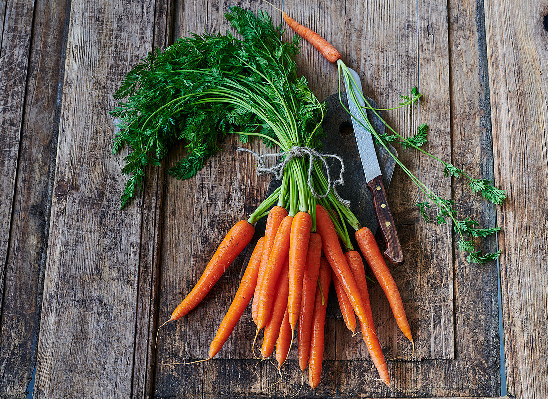 Bunch of carrots with a knife on a rustic wooden background
