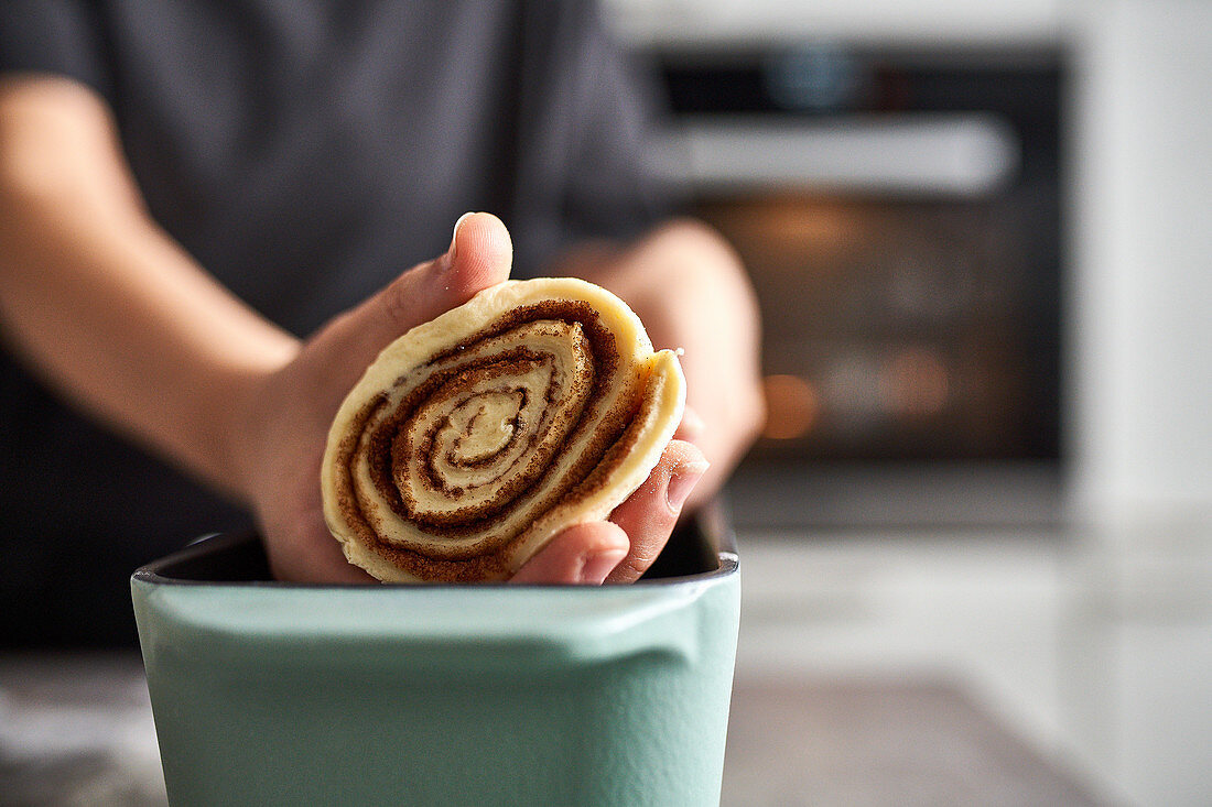 Preparing cinnamon roll cake: placing a rolled cake in a baking pan