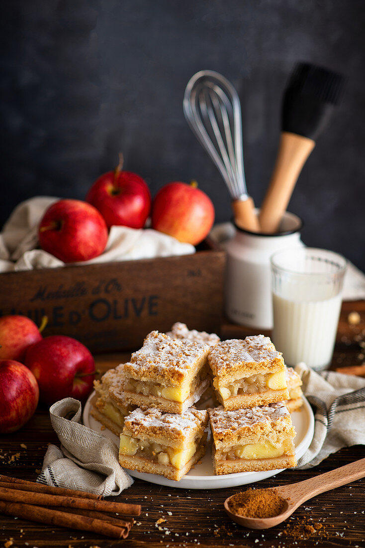 Sliced apple pie with glass of milk and apples
