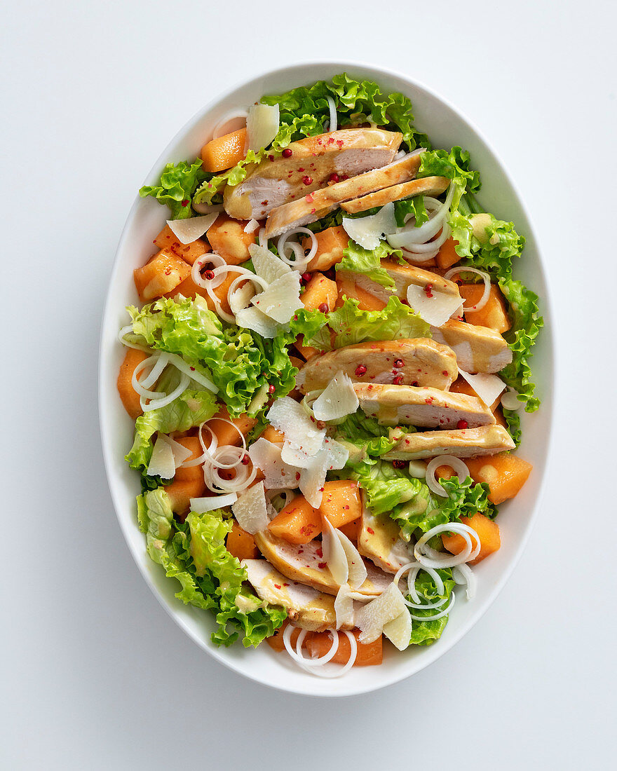 A mixed leaf salad with roast chicken breast, melon and mint