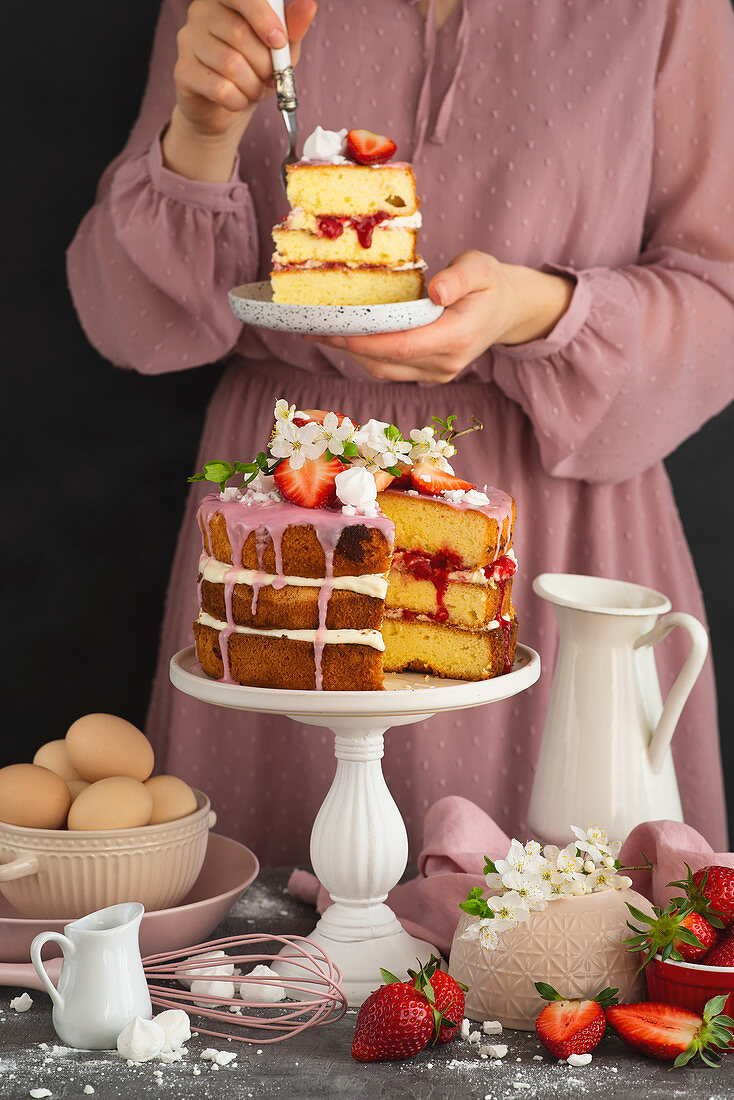 Woman tasting rustic sponge cake with whipped cream and strawberry sauce