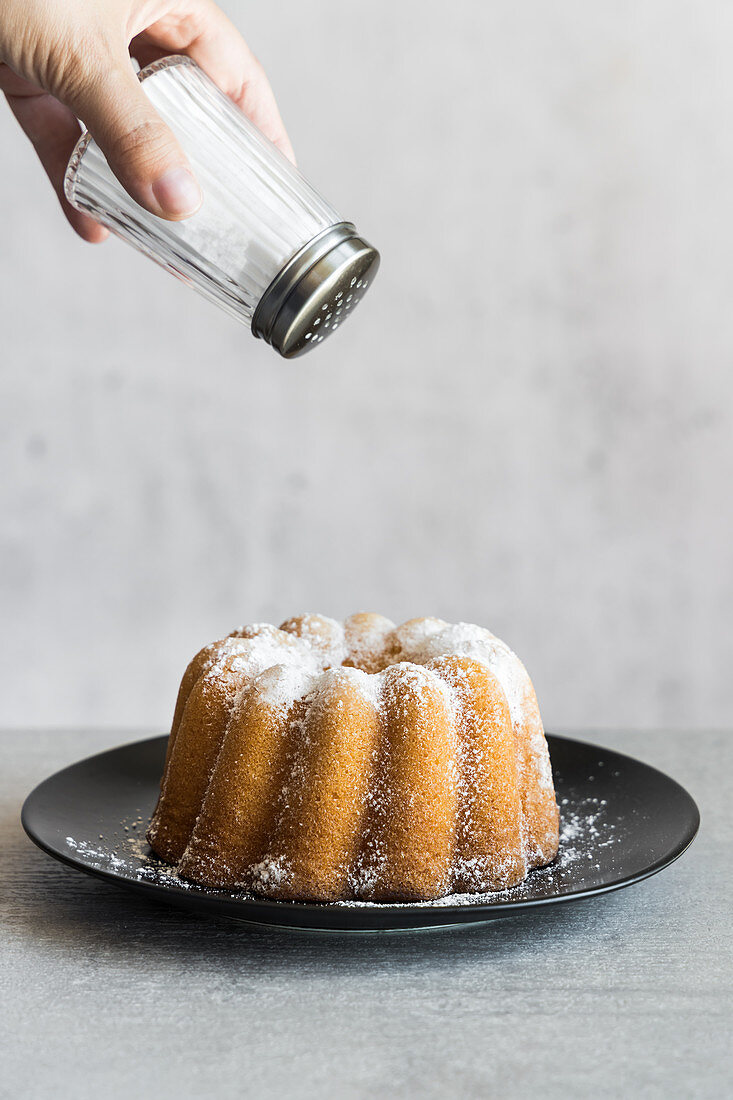 Dusting bundt cake with powdered sugar