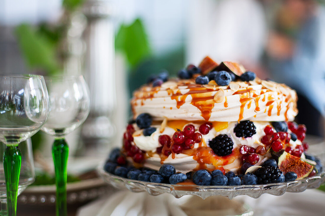 Meringue cake with autumnal berries on a cake stand