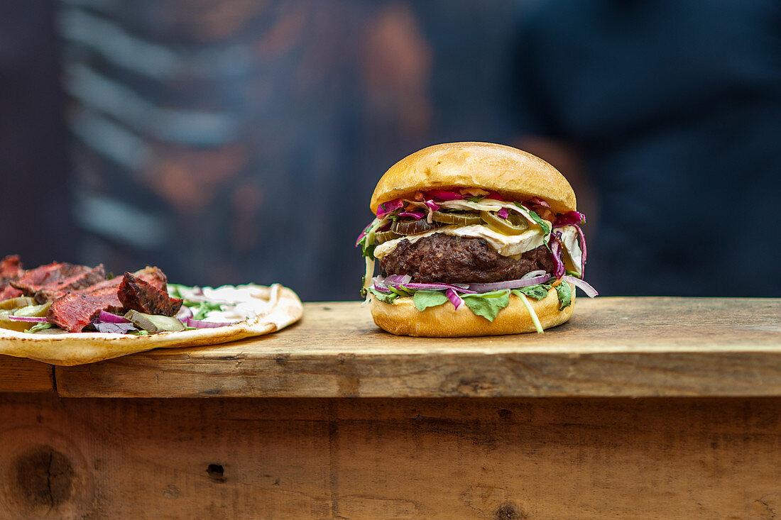 A hamburger and a tarte flambée on wooden counter