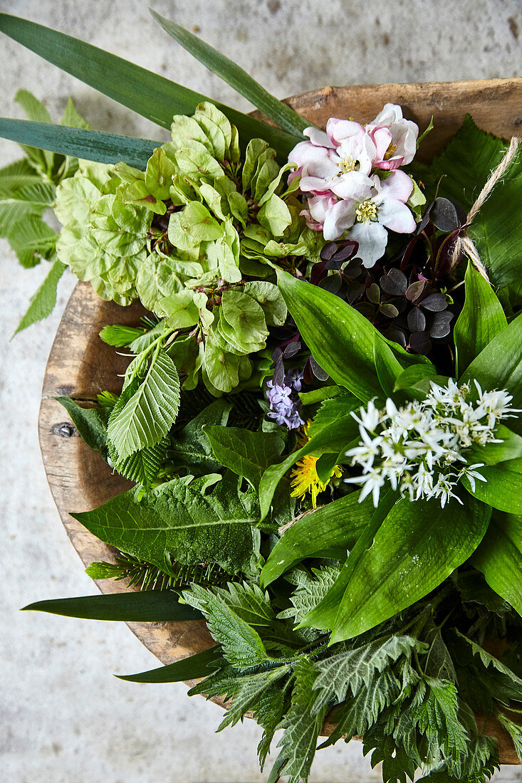 A spring flower arrangement in a wooden bowl with wild garlic, dandelions, fruit blossom and beech twigs