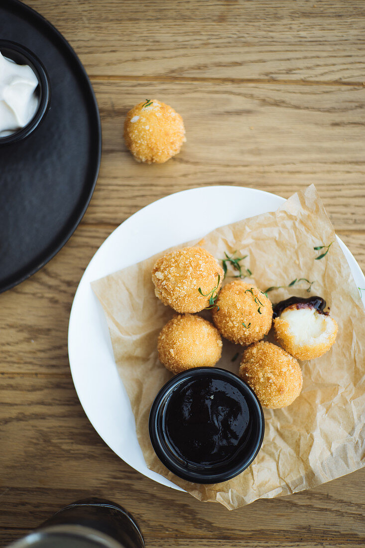Delicious potato balls with cheese filling served with sauce on plate on wooden table