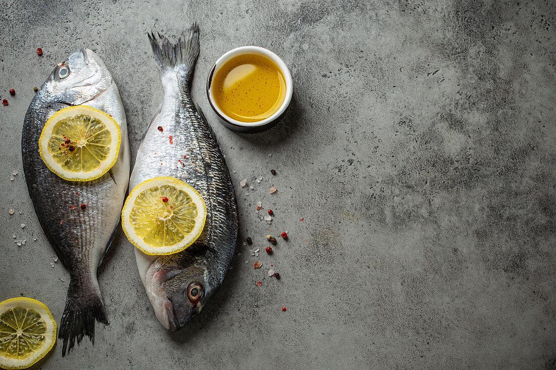 Raw fresh fish dorado with lemon wedges, olive oil and seasonings