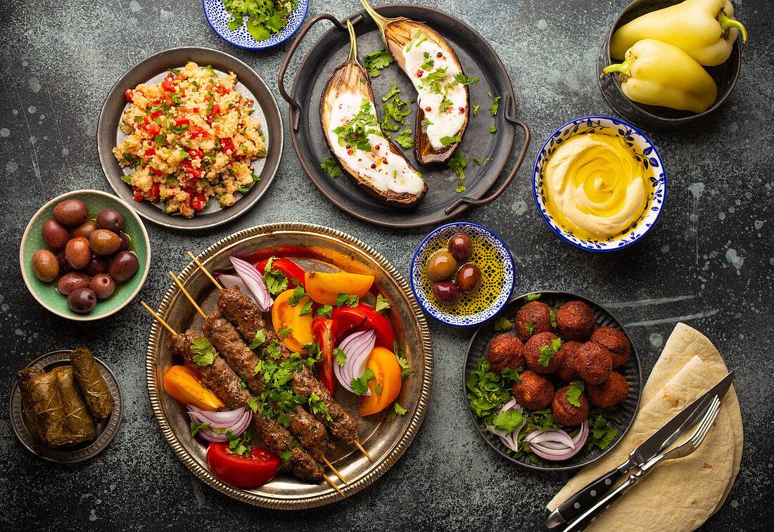 Middle eastern dinner with grilled kebab, falafel, roasted and fresh vegetables