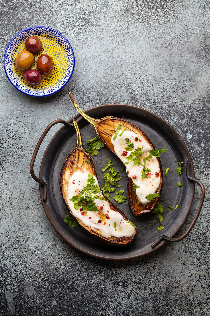 Grilled eggplant served in a pan with yoghurt, fresh cilantro and seasonings