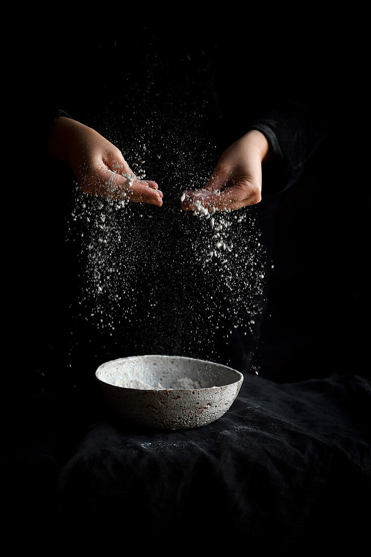 Flour being sprinkled from hands on a dark background