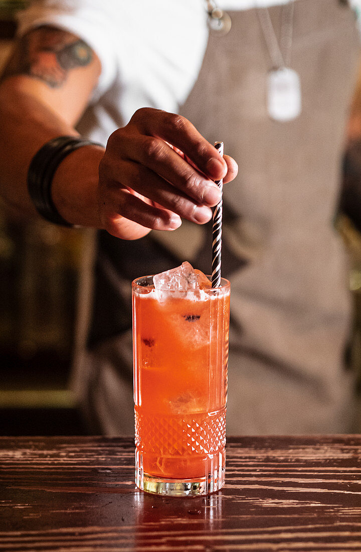 Unrecognizable bartender putting straw in glass of cold fruit cocktail during work in bar