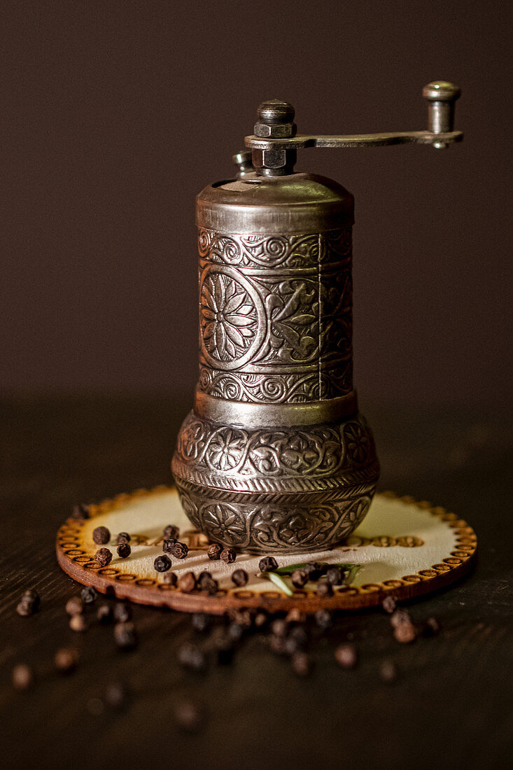 Vintage metal mill with ornament and pepper seeds placed on table on brown background