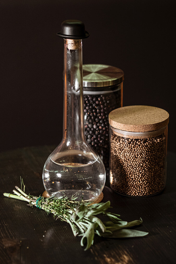 Bunch of fresh herbs placed on table near bottle of vinegar and jars with spices on black background