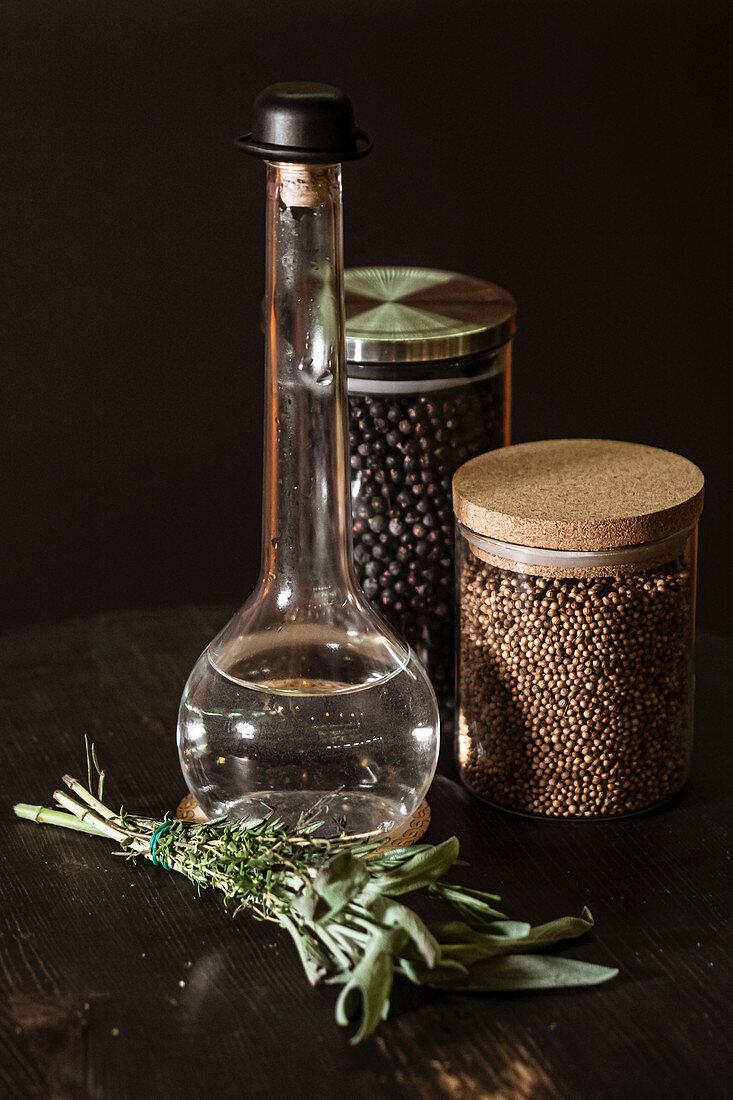 Essigflasche, frische Kräuter und Gläser mit Gewürzen