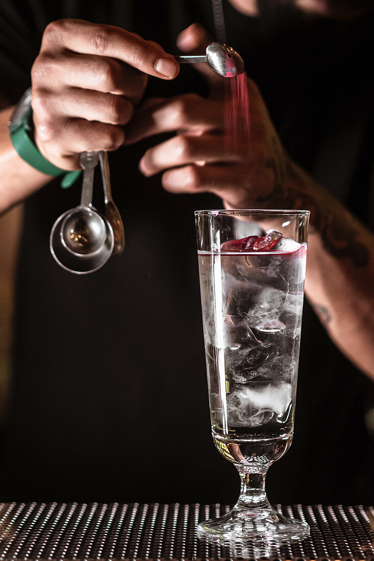 Unrecognizable male bartender adding ingredient into glass with alcohol cocktail with ice cubes while preparing drink in bar