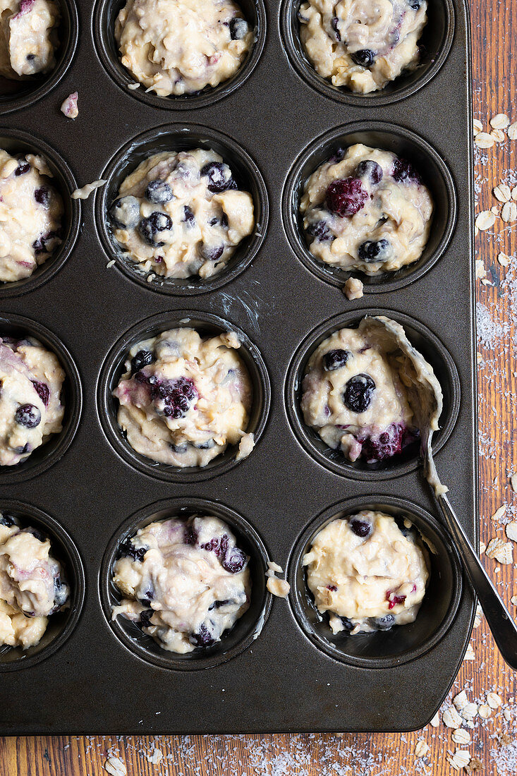 Mixed berry and oat muffin batter spooned into a patty cake pan
