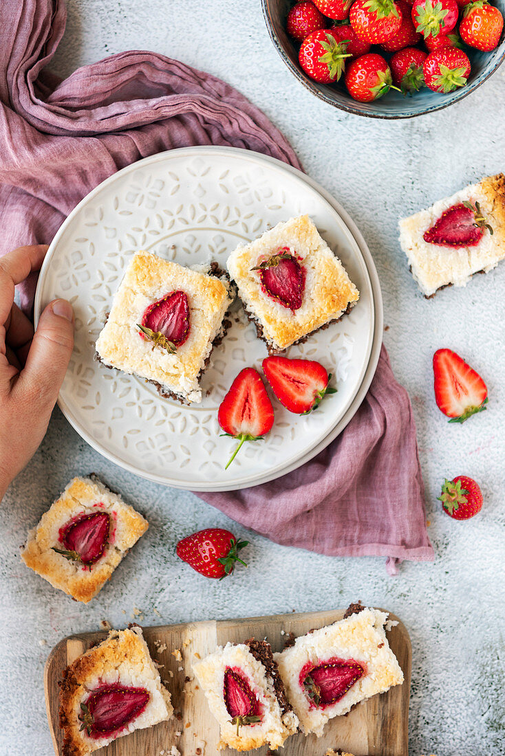 A hand holding a white plate with two slices of coconut ice squares with chocolate bottom and strawberry topping