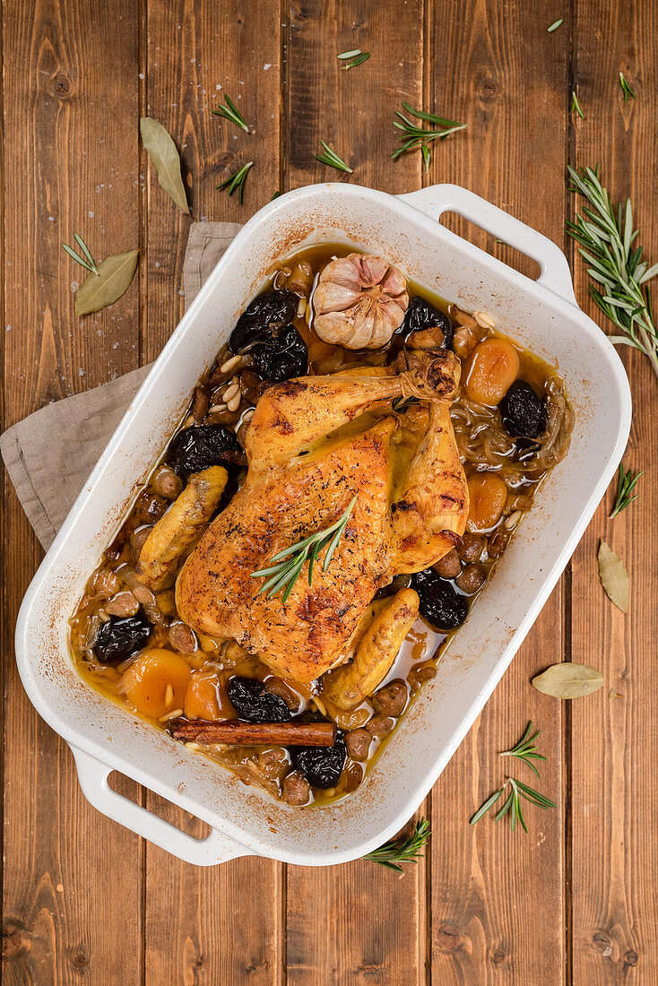 Stuffed baked chicken in dish with garlic and cinnamon stick placed on wooden table