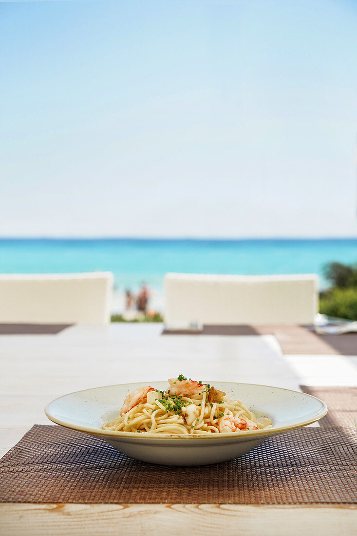 Round plate with spaghetti placed on wicker mat on table with view of ocean in sunlight on background