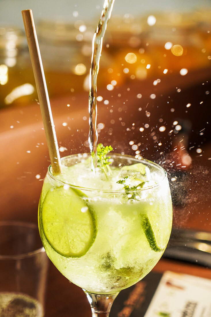 Splashing flow of alcoholic mojito cocktail in crystal glass with lime slices