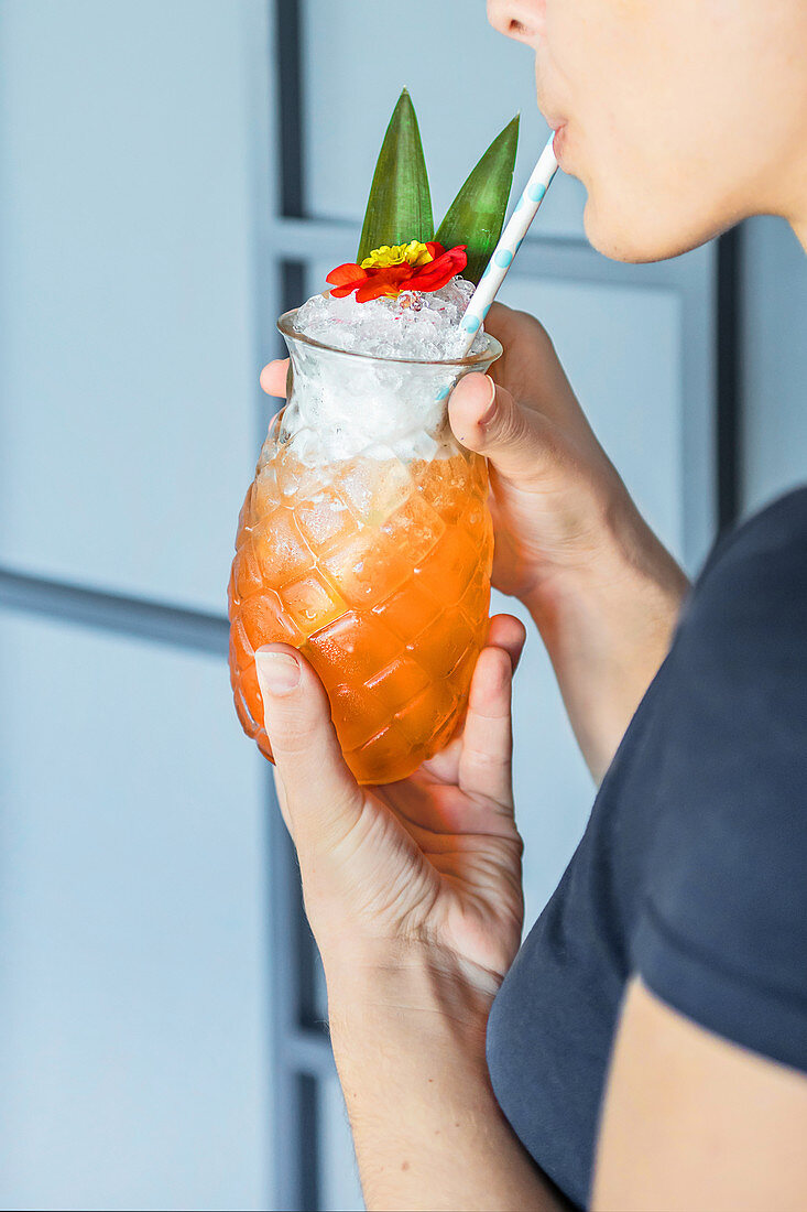 Faceless female sipping cool cocktail with straw from glass in shape of pineapple