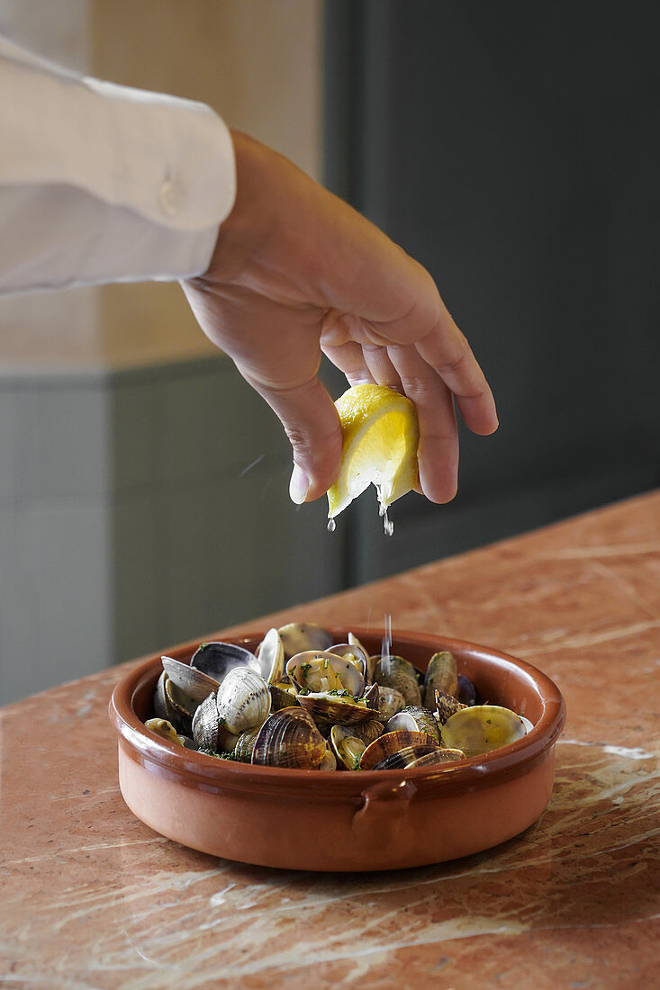 Faceless person in white shirt squeezing lemon slice over bowl of delicious freshly cooked mussels