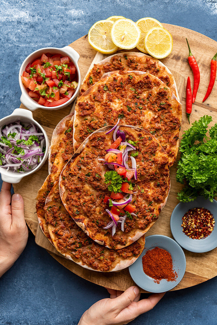 Woman holding a wooden board with Turkish lahmacun with red onion salad and tomato salad as condiments