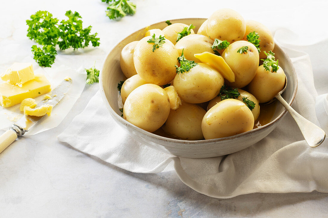 Whole steamed potatoes with butter and parsley in a ceramic bowl