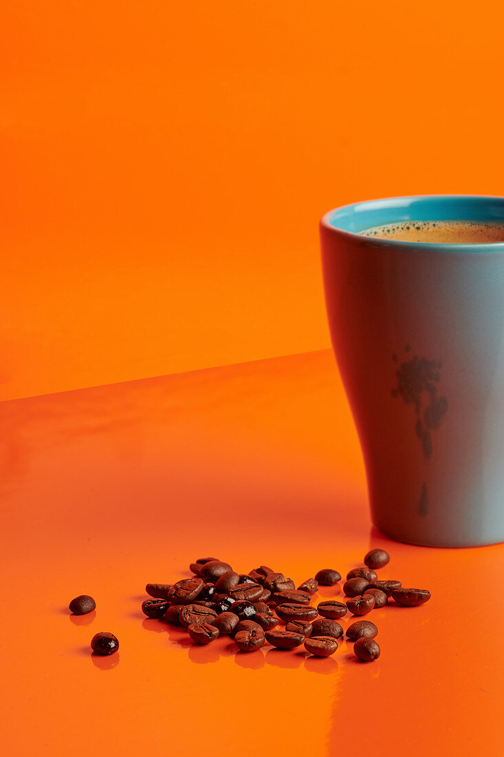 Mug of delicious hot drink arranged on table with aromatic coffee beans on orange background