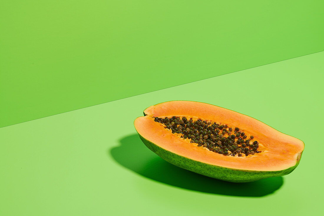 Fresh ripe halved papaya with seeds placed on bright green background