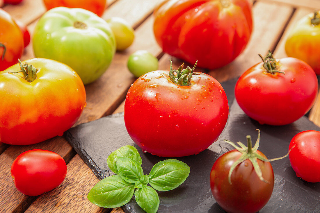 Variety of organic tomatoes on wooden table