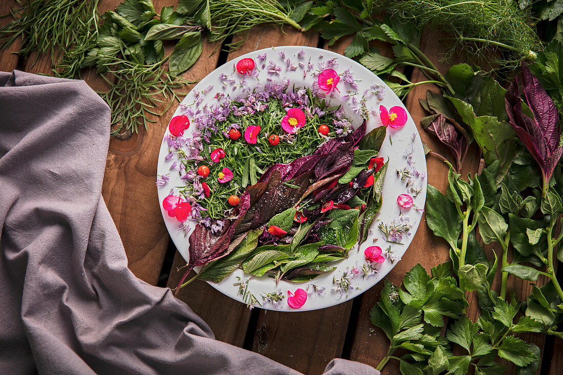 Creative composition of delicate flowers and delicious green herbs placed on wooden table with napkin