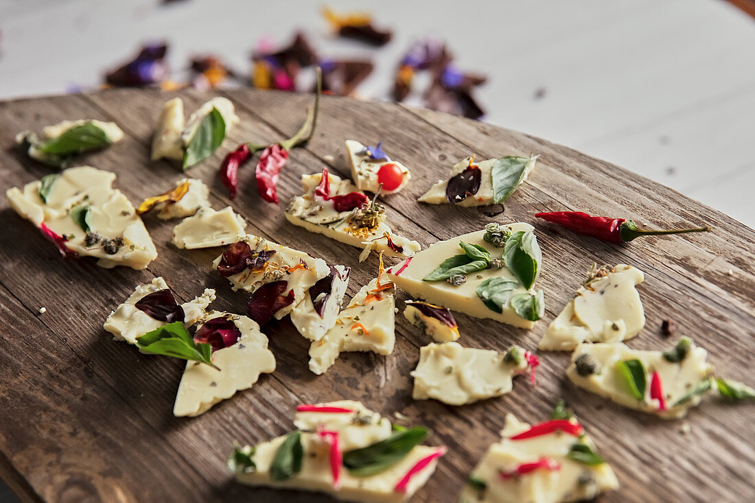 Pieces of tasty chocolate with various flower petals and herbs placed on wooden table