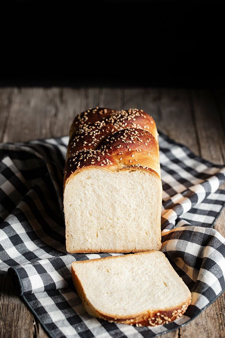 Loaf of fresh bread with sesame placed on cloth cutting board in kitchen on black background