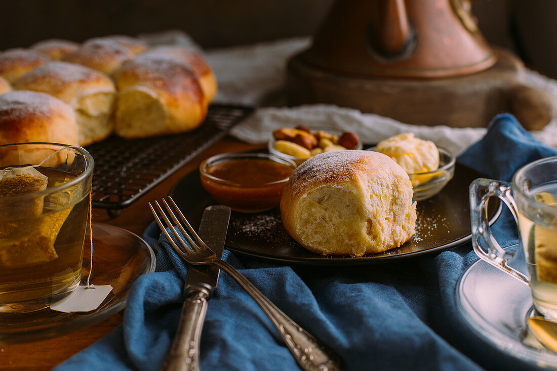 Ceramic plate with fresh bun and small bowls with mix of nuts near jam and butter close to cup of green tea on crumpled towel
