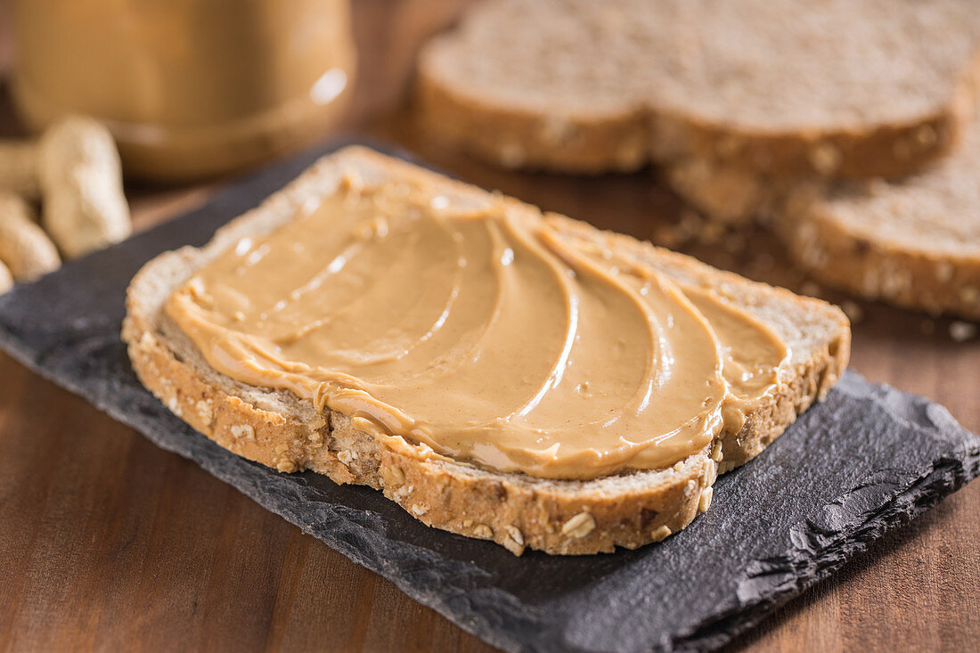 Piece of bread with peanut butter placed on black slate broad on wooden table with knife and fork