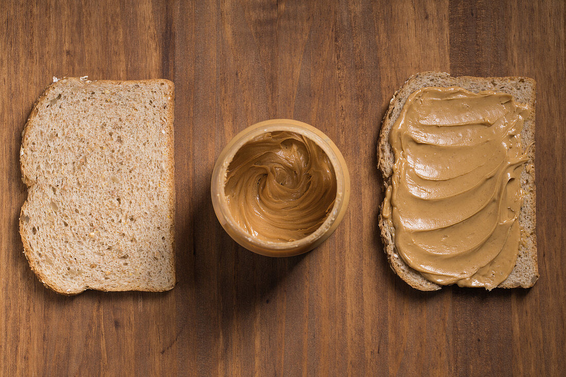 Bread slices with creamy peanut butter placed on wooden table in kitchen with jar