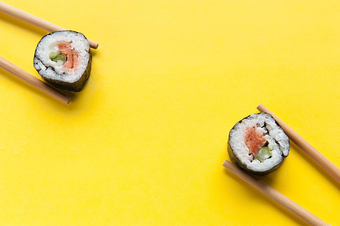 Maki-Sushi mit Lachs zwischen Essstäbchen auf gelbem Untergrund