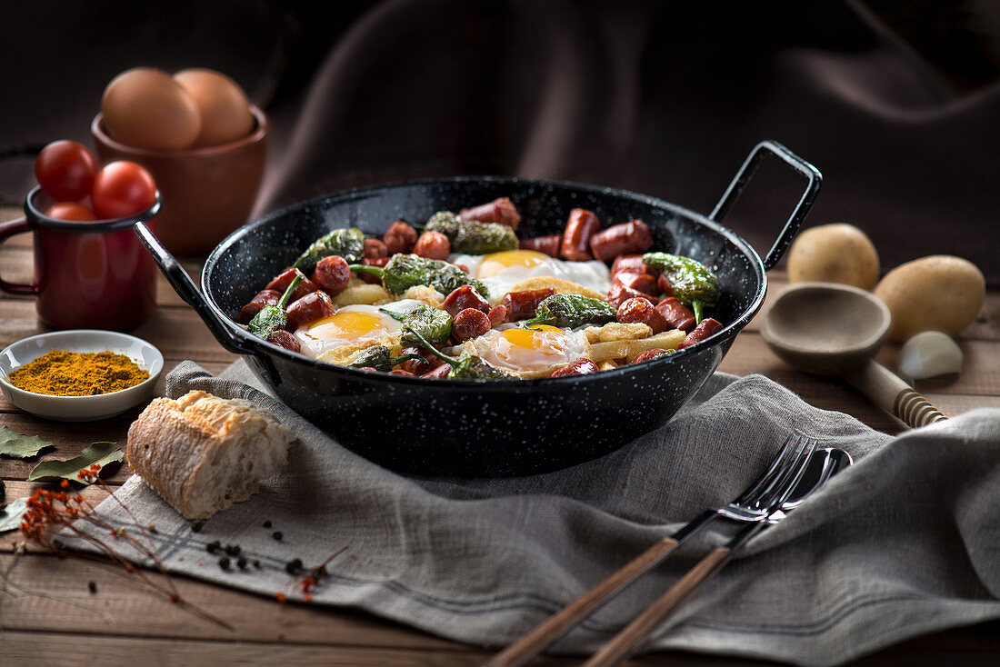 Pan with fried eggs with traditional Spanish chorizo sausages and green peppers