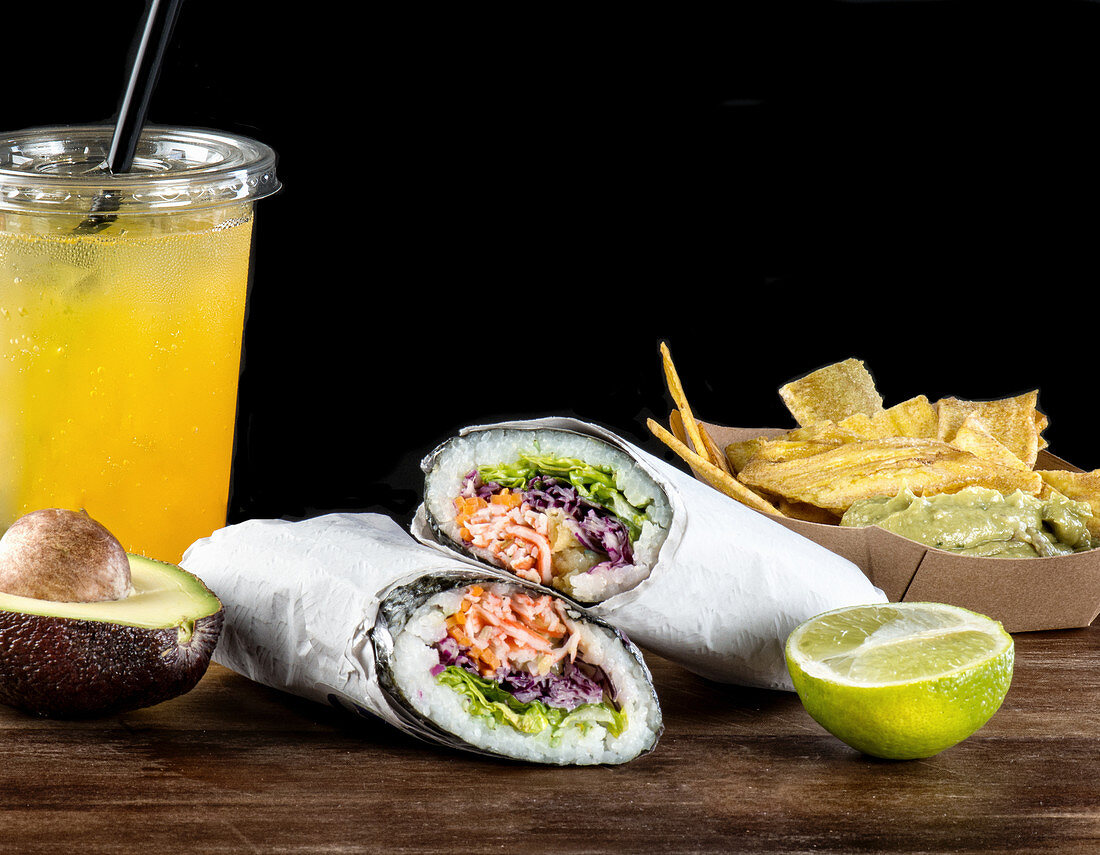 Mexican snacks including fried plantains with guacamole and sushi burritos served with traditional cold fruit soda