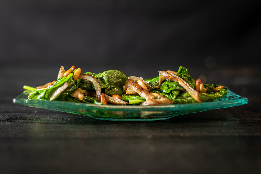 Glass plate of tasty spinach salad with mushrooms placed on black wooden table in cafe